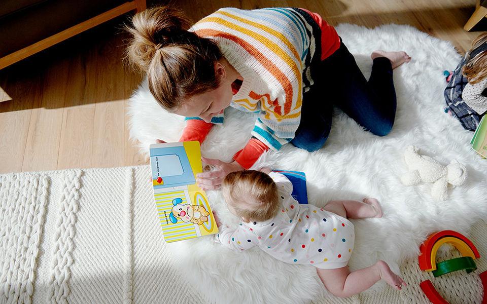 mum reading to baby on floor